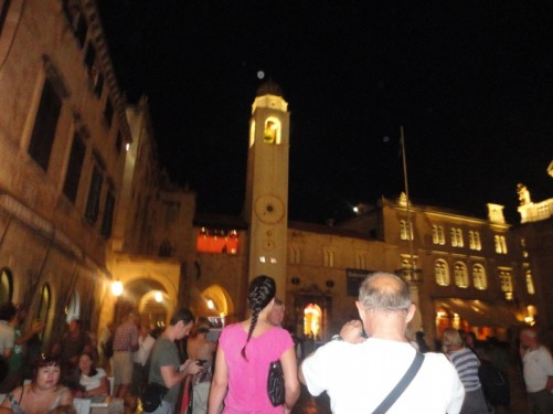 Evening view across crowded Luža Square. View of a tall bell tower at the side of the square.