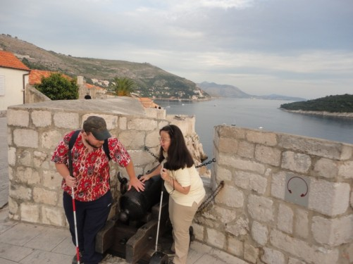 Tony and Tatiana touching the canon. A picturesque view of the coastline in the background.