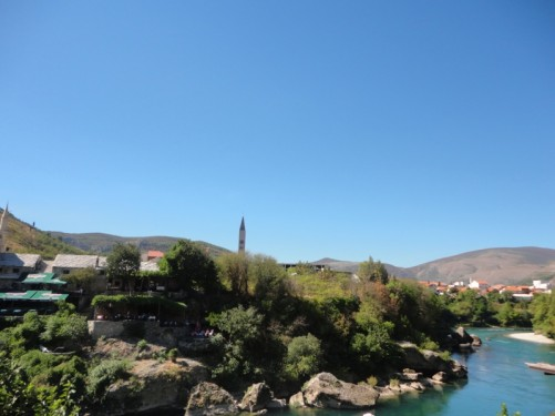 View down to the rocky tree-lined banks of the Neretva river. Cafés and restaurants above it on the far bank.