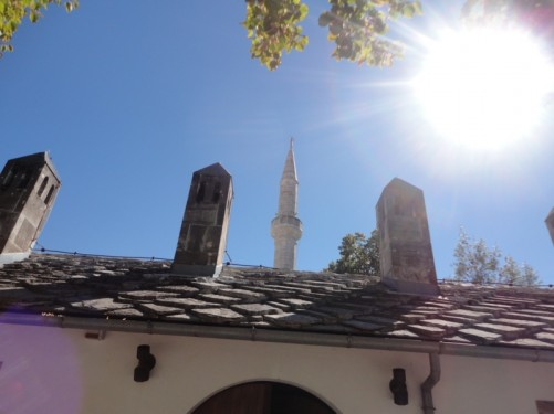 The minaret of the 17th century Koski Mehmed-Pasha Mosque standing up behind a building.