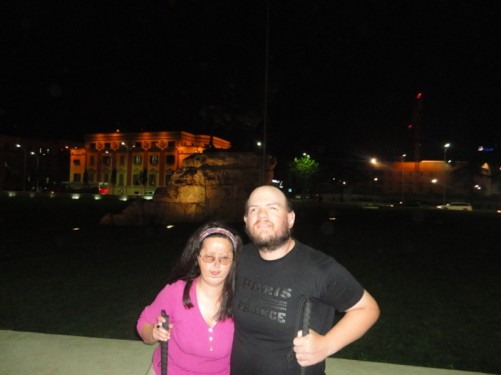 Tony and Tatiana in Skanderbeg Square during the evening. A statue of Skanderbeg on horseback is just discernible in the gloom.