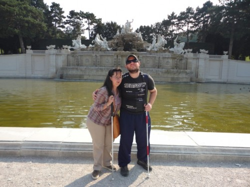 Tony and Tatiana at the Neptune Fountain. In front is a large formal pond and behind is a white marble platform with statues on top. A statue of Neptune stands at the centre. This huge fountain was completed in 1780.