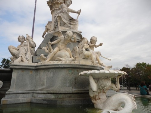The Athene Fountain located in front of the Parliament Building. Various statues can be seen around the base, including a cupid riding on a dolphin and a mermaid holding a large shell aloft.