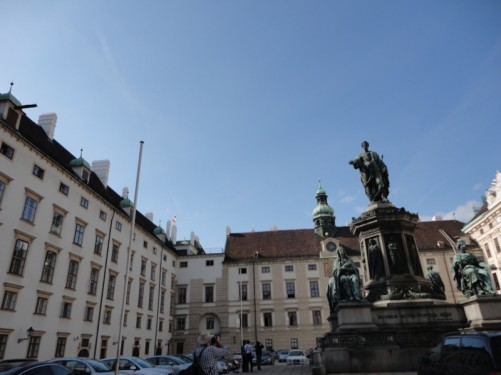 Closer view of the Emperor Franz Joseph I monument. The wing of the palace in the background is the Amalienburg. There is a dome on the roof, a clock face on a small tower in front and an unusual astronomical clock below. The offices of the President are located in this wing.