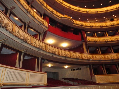 The back of the auditorium. Gold-coloured moulding on the front of the balconies.