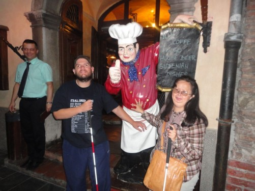 Evening. Tony and Tatiana outside Sokol restaurant touching a model of a chef holding a menu board.