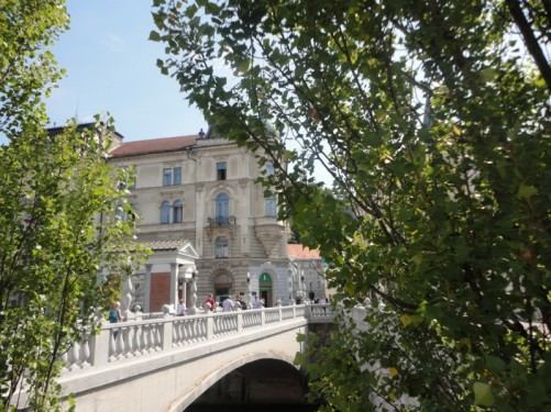 View of the Triple Bridge from between trees. Looking towards the old town.