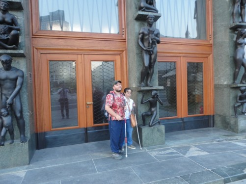Tony, Tatiana, outside the Slovenian Parliament building. The main doorway incorporates an impressive surround of bronze sculptures: nude figures all performing tasks or holding objects.