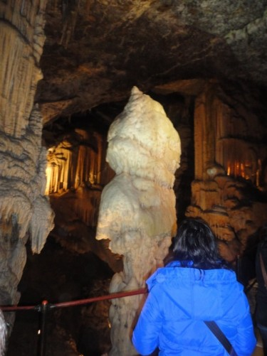 Looking from a platform at an enormous stalagmite standing in front.