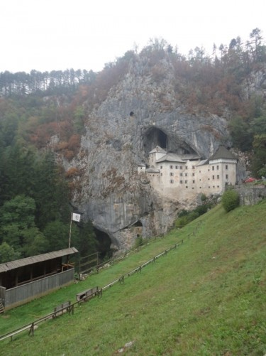 Looking towards Predjama Castle. This 700-year-old castle is built into the mouth of a large cave with a towering cliff face above.