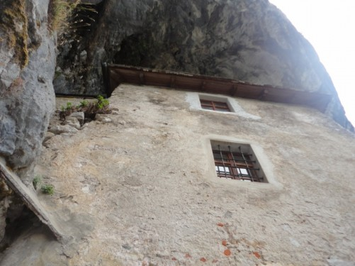 Part of the castle's exterior. Walls built into the cliff and a mass of rock overhanging above.