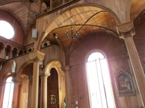 Another view of the cathedral's interior. Wooden columns and a tall window behind.