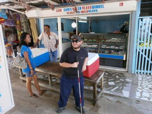 Tony at the market outside Oom Sam's Vis en Vlees Winkel (Uncle Sam's Fish and Meat Shop).