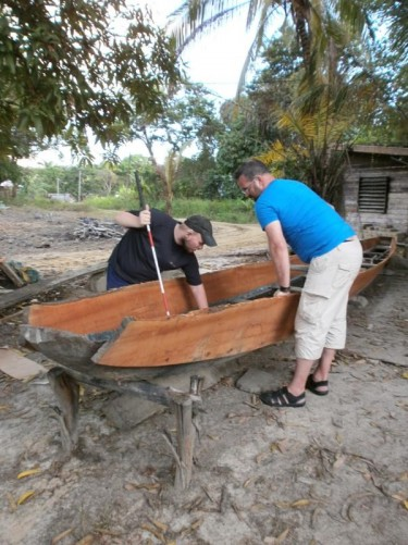 Tony back on dry land examining another traditional wooden canoe. In a small village or hamlet where traditional boat building is undertaken.