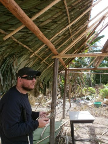 Inside a traditional house under construction in the Amerindian village. Tony holding some twine.