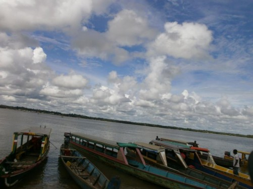 View across the Maroni river on the border between Suriname and French Guiana. A row of boats moored along the bank.