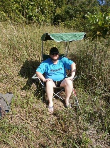 Tony outdoors sitting on a chair with a sun shade. Quite long grass under-foot and denser vegetation behind.