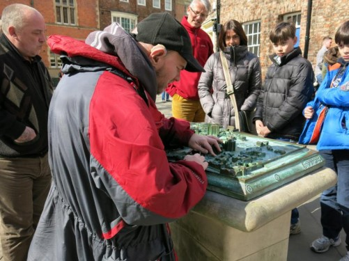Tony examining a bronze model of York Minster and the surrounding area. The model includes labels in Braille. It is located in front of the Minster itself.