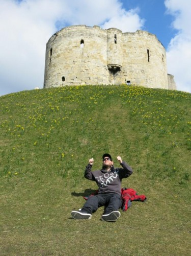 Tony sitting on the grass covered mound of Clifford's Tower.