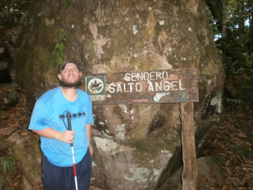 Tony by a large boulder and a sign that reads 'Sendero Salto Angel' (Angel Falls trail). It's known as Parekupa-meru by the local Pemon Indians, but gained the Angel name after US pilot Jimmy Angel crash-landed on the Auyan Tepuy whilst searching the area for gold in 1937.