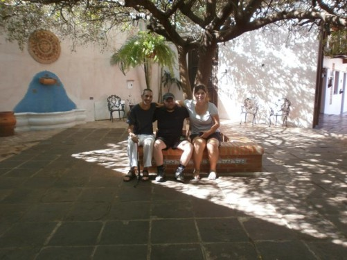 Tony sitting with a young French couple under a tree in a courtyard.