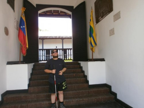 House of the Congress of Angostura. Tony at the foot of steps leading through the building into a courtyard. Flags at either side: one the Venezuelan national flag and the other of Bolívar State.