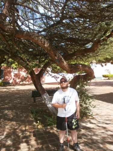 Tony standing under the shade of a tree in Plaza San Clemente.