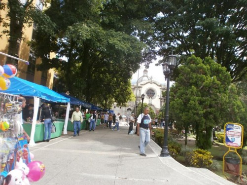A pedestrian route lined with market stalls in Plaza Bolivar heading away from the cathedral.