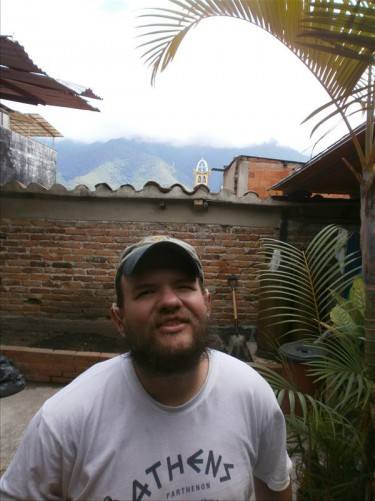 Tony back at the hostel in the garden by a tall fern. Away in the distance Mount Bolivar (or another one of the Andes mountains surrounding the city) can be seen rising up and disappearing into the cloud.
