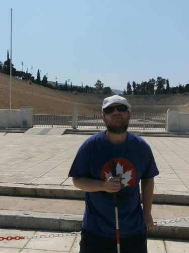 Tony at the Panathenaic Stadium. This ancient stadium once hosted the Panathenaic Games, in honour of the Goddess Athena. It originally sat in a natural hollow between the hills of Agra and Ardettos. It was constructed in marble in 329 BC. During the second half of the 19th Century the ruins of the stadium were excavated and subsequently rebuilt to host the athletics at the first modern Olympic Games in 1896. Unlike modern stadiums, it has a long narrow hairpin-shaped design, with seating around three sides.