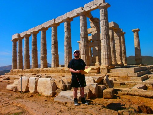 The ancient Temple of Poseidon at Cape Sounion – a promontory located approximately 69 kilometres (43 miles) south south-east of Athens, at the southernmost tip of the Attica peninsula. The ruins comprise 15 standing columns, engraved with many names, including English Romantic poet, Lord Byron. Tony is standing in front holding a Braille guidebook.