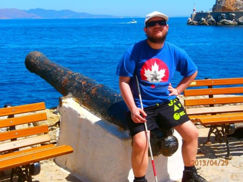Tony sitting on an old canon with a view across the Gulf of Hydra to the mainland beyond.