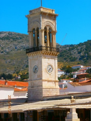 A marble clock tower centrally located at the back of the harbour and in front of Hydra's cathedral and the Monastery of the Assumption.