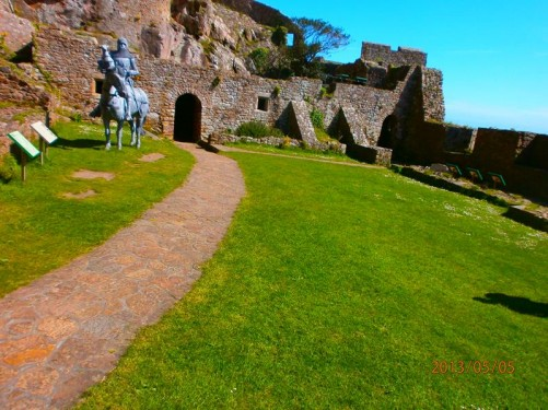 An area of grass enclosed by walls and battlements. A metal sculpture of Sir Hugh Calvely dressed in armour and on horseback in front. He was a 12th century English knight and commander, who took part in the Hundred Years' War.