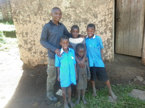 Julius Asaba, one of the managers of Enfuzi Community Campsite, with four kids. Standing in front of the mud wall of a hut. The kids are orphans who live and go to school at the nearby orphanage. It's run by a Pastor John Bosco.