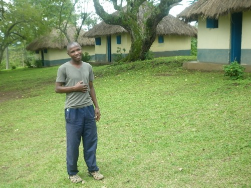 Julius Asaba standing in an area of grass in front of three huts with thatched roofs.