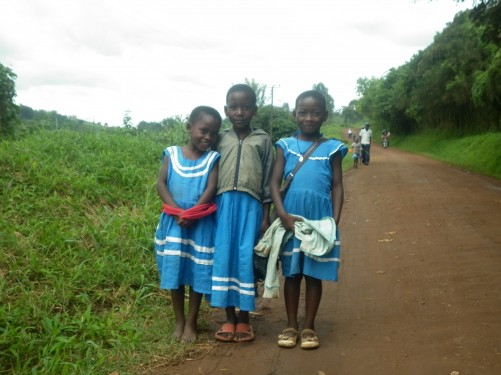 Three girls in school uniform on a unpaved road. Other people further away walking along the road.