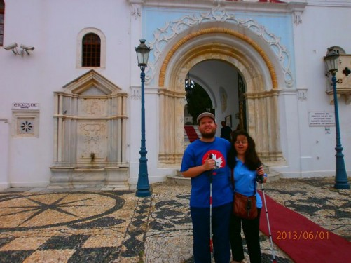 Tony and Tatiana outside the entrance to Panagia Evangelistria. The church was built around an icon, which many miracles have been attributed to. According to tradition the icon was found after the Virgin Mary appeared to the nun St. Pelagia and revealed to her the place where the icon was buried.