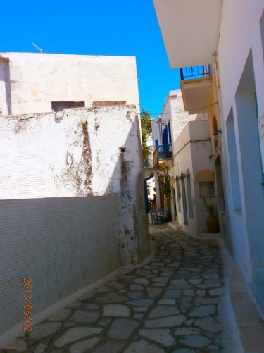 A narrow street lined with traditional white-painted houses.