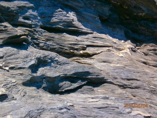 Close-up section of a rocky cliff. The strata deformed into interesting shapes.