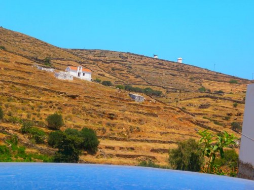 A closer shot towards the hill, which is covered with yellowed grass and traditional stone walls. A small church half way up. Two traditional windmills can just be seen right on the ridge of the hill.
