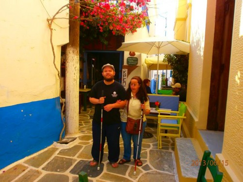 Tony and Tatiana in another narrow street with a tall shrub with red flowers hanging above. Couple of small café tables behind them.