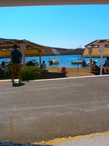 View across a road to the beach and sea. Shaded café tables on the beach.