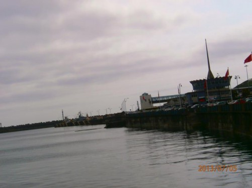 Now looking the other way towards Douglas Harbour. To the right, the round central part of the Sea Terminal building can be seen, with a tall narrow concrete spire protruding from its centre. This construction is sometimes known as the 'lemon squeezer' because of its shape.
