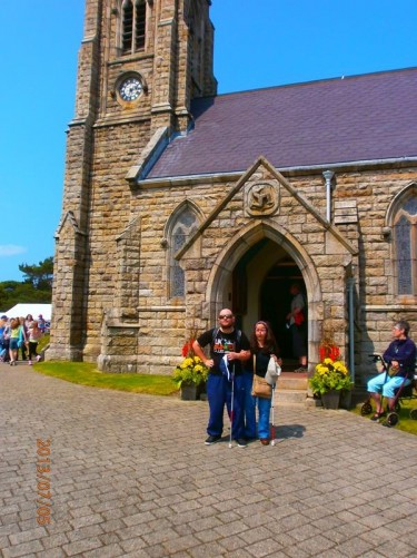 Tatiana and Tony outside the Royal Chapel of St John the Baptist. The chapel is located close to Tynwald Hill and also the village of St John.