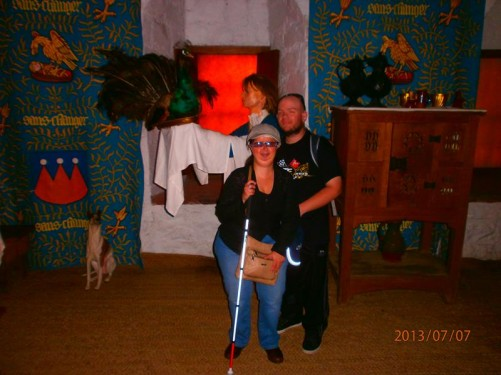 Tony and Tatiana in front of another historic scene. A female manikin carrying a peacock on a tray. There is also a thin-looking dog to the left and a large cupboard to the right.