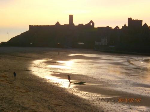View across the beach in Peel Bay. On the far side, Peel Castle, lit by the setting sun.