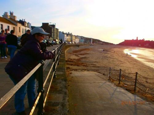 Tatiana looking across the beach from railings on the promenade.