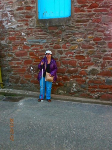 Tatiana leaning against a reddish coloured stone wall.