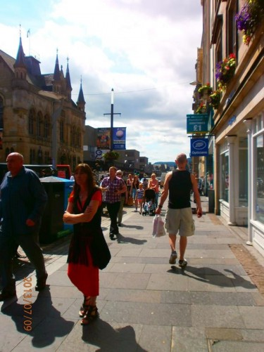 View from High Street down along Bridge Street. This is a busy shopping street. The building on the left with decorative towers on the roof is the Town House.